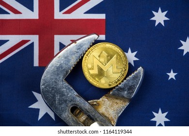 Monero coin being squeezed in vice on Australia flag background; concept of cryptocurrency monero (xmr) under pressure. Prohibition of cryptocurrencies, regulations, restrictions or security