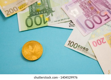 Monero coin next to Euro bank notes on blue background. Digital currency, block chain market. Euro bills next to crypto coin