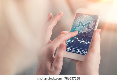 Monero symbol on mobile app screen with big BUY and SELL buttons. Monero cryptocurrency on stock market. New digital money.