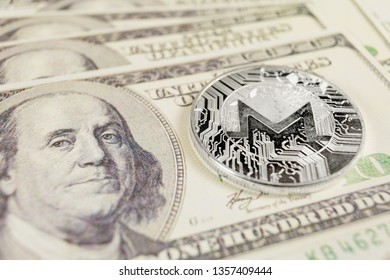 MONERO XMR cryptocurrency - silver monero coin on the background of Dollar bills