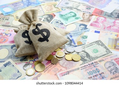 Monetary inflation / interest rate control concept : Money in hessian bags on US USD dollar notes or bills and coins from around the world e.g Indian rupee, Chinese CNY yuan, EU euro, Japanese JPY yen