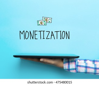 Monetization concept with a tablet on blue background