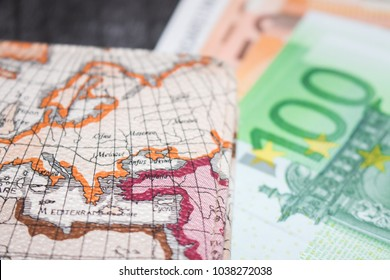 Money, Airplane ticket and map. Eurobanknotes with boarding pass and map, on black wooden background. Business and travel planning concept.