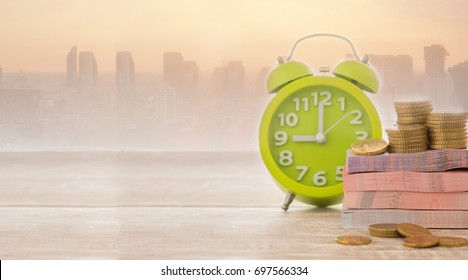 Money, alarm clock with city business background. Concept of retirement funds,finance, time is money.