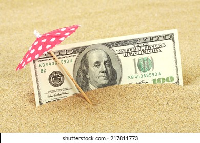 Money american hundred dollar bills in the beach sand under red and white dots sunshade