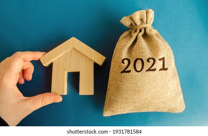 Money bag 2021 and a wooden house. Real estate concept. Family budget planning. Investments, plans, savings. Mortgage and mortgage rates. Forecasts. Loan. Refinance home