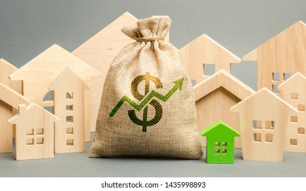 Money bag with arrow up and miniature wooden houses. The concept of rising property prices. High mortgage rates. Expensive rental apartment. Growing demand for home purchase. Real estate market.
