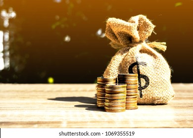 Money bag and coins on orange light background present the savings planting. or savings to buy a home or real estate. Or show divide the investment. Loan Or for the future Concept of money
