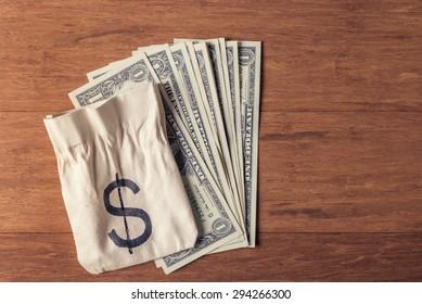 Money bag and dollar bills over wooden background