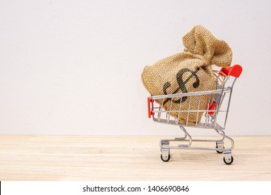 Money bag and dollar symbol in shopping cart, Shopping cart on wooden table presenting Using money to shop in a supermarket or market or online marketing. Money concept. - image