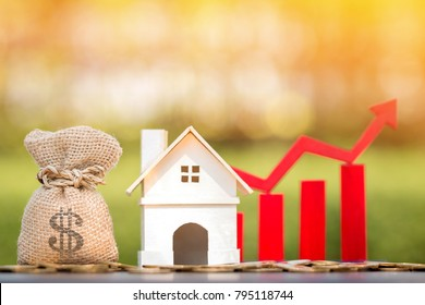 Money bag and home and red arrow and bar graph with growing value put on the coin on bokeh background in the public park, for currency and financial business investment and fund real estate concept.