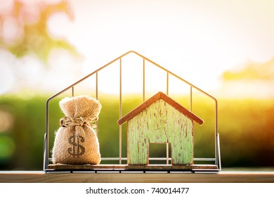 Money bag and house model put in the shelf with shape home on grass on sunlight in the public park, for Business investment loan or for save money for buy a new real estate concept.