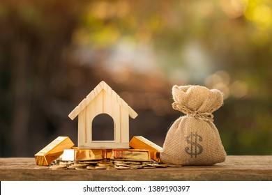 Bolsa de dinero con presentación y modelo de casa puesto en la barra de oro y la moneda con creciente interés en el parque público, Ahorrando dinero para comprar casa o préstamo para la inversión del concepto de bienes raíces.