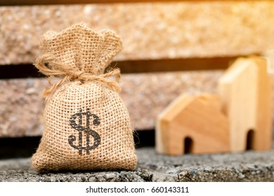 Money bag put on the cement mortar floor on the home with blur background,Loans for real estate or save money for buy a new house to family concept.
