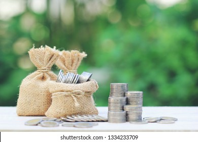 Money bag with stack of coins money on natural green background, Saving for prepare in future and Business investment concept