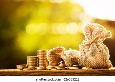 Money bag and stacking golds coin with grow up on the wooden  in the public park for loans to planned investment in the future concept.
