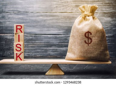 Money bag and wooden blocks with the word Risk. The concept of financial risk. Justified risks. Investing in a business project. Making the right decision. Property insurance. Legal and market risks