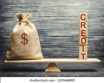 Money bag and wooden blocks with the word Credit on the scales. The concept of a successful loan. Correction and formation of credit history. Refinancing credits. Favorable interest rates.