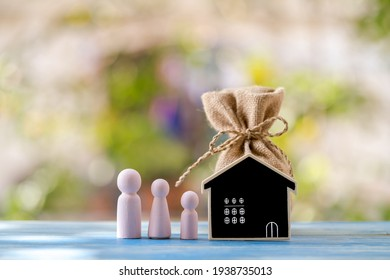 Money bag and wooden family and blackboard is home put on the wooden plate vintage blue in the public park, Loan for business investment real estate concept.