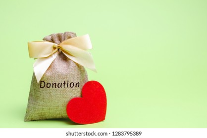 A money bag with the word Donation and a red heart. Accumulation of money for a medical donation. Health care. Saving. Social medical help from volunteers. Charitable foundation