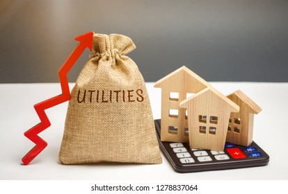 Money bag with the word Utilities and an up arrow and houses on a calculator. The concept of raising prices for the use of utilities. Payment of bills. Rising prices for water, electricity and heating