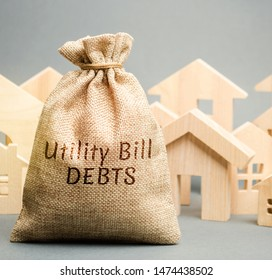 Money bag with the words Utility bill debts and wooden houses. Fines and penalties for failure to pay the debt for electricity and gas. Register of debtors. Stopping the provision of utilities.