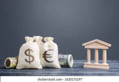 Money bags and a bank building. Saving money, deposit. National economy, investment and currency accumulation. Leasing and loans, registered capital. Tax and taxation. State debt. Project sponsorship