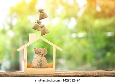 Money bags and drop on the top in the wooden home model put on the old wood in the public park, Saving money for buy a new house or loan for plan business investment of real estate concept.