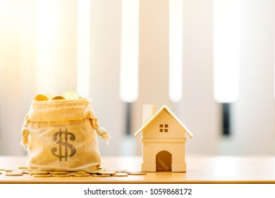 Money bags of gold coin and a model home put on the desk in the office, Saving money or loan for business investment real estate of owner in the future and buying a new home concept.
