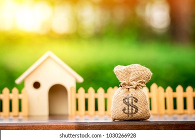 Money bags and a model home put on the table in the public park, Saving money or loan for business investment real estate of owner in the future and buying a new home concept.