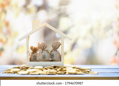 Money bags put in the wooden home model put on the gold coin put on the old wood in the public park, Saving money for buy a new house or loan for plan business investment of real estate concept.