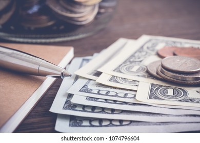 Money banknote US dollar and coins put on wooden table with silver pen, notebook and saving jar on background, vintage style. Currency, financial economy, earning income, budget management concepts