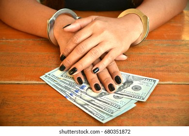 Money bills under the hands of a cuffed female suspect