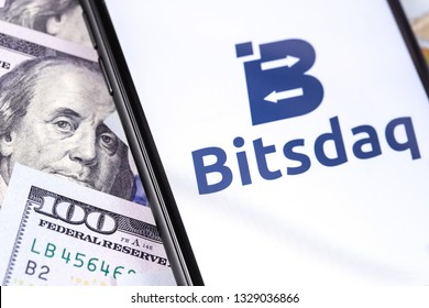 Money, and Bitsdaq cryptocurrency exchange logo displayed on smartphone. Moscow, Russia - March 1, 2019