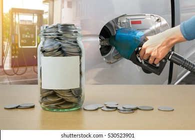 Money bottle with coins, Hand holding Fuel nozzle pouring background