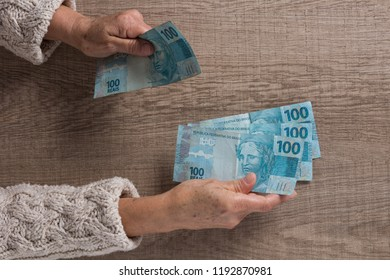 Money from Brazil, brazilian currency. Above view of old retired person paying in cash