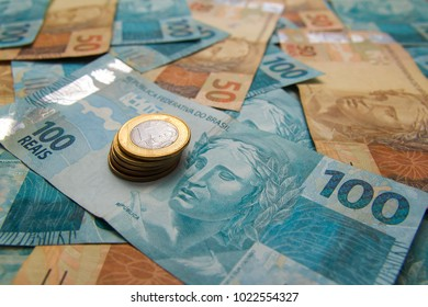 Money from Brazil. Notes of Real, Brazilian currency. Concept of economy, inflation and business. Lots of money spread on the table. Background.
