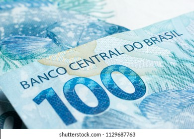 Money from Brazil. Notes of Real, Brazilian currency. Concept of economy, inflation and business. Macro photography 100 Reais bill. Text written Banco Central do Brasil (Central Bank of Brazil)