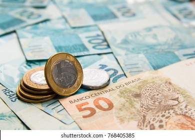 Money from Brazil. Notes of Real, Brazilian currency. Concept of economy, inflation and business. Full frame with money banknotes and One Real Coin the foreground.
