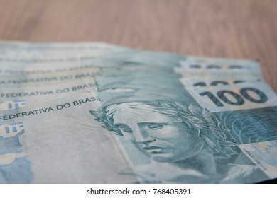 Money from Brazil. Notes of Real, Brazilian currency. Concept of savings, salary, payment and funds. Portrait with selective focus of the Effigy of the Republic in a note of 100 Reais. Space for text.
