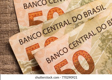 Money from Brazil. Notes of Real, Brazilian currency. Concept of economy, inflation and business. Group of bills on wooden table