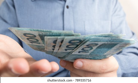 Money from Brazil. Notes of Real, Brazilian currency. Concept of finance, investment, wealth. Man offers cash bills.