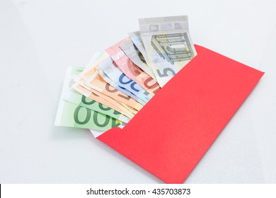 Money in a bright red envelope, isolated on white background.