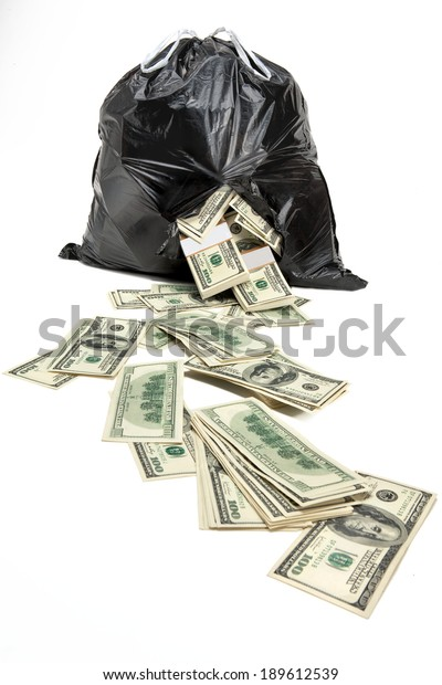 Money in the broken bag / studio photography of black plastic bag with hundred dollar bills on a white background