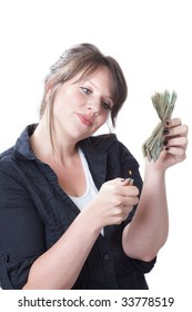 Money to burn; woman ready to light a stack of money on file; isolated on a white background.