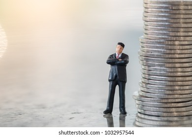 Money and Business Concept. Businessman miniature figure standing on ground with stack of silver coins.