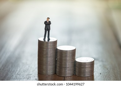 Money and Business Concept. Businessman miniature figure standing on stack of silver coins on wooden table.