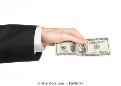 Money and business topic: hand in a black suit holding dollars banknotes isolated on white background in studio