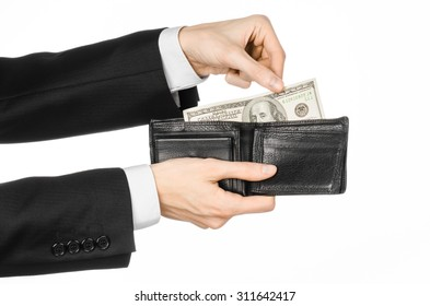 Money and business topic: hand in a black suit holding a wallet with dollar banknotes isolated on white background in studio