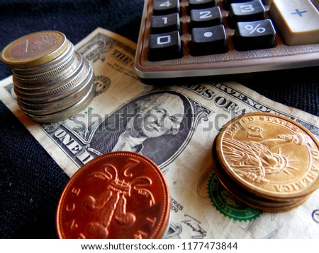 Us money background with a blue calculator on top stock photo.